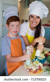 Portrait of young smiling mother with her son who standing in cook form in the kitchen and salting and peppering salad