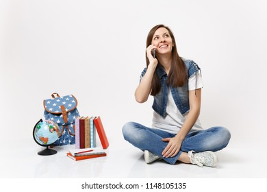 Portrait of young smiling pensive woman student talking on mobile phone looking up sitting near globe, backpack, school books isolated on white background. Education in high school university college