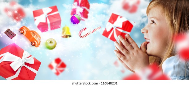 Portrait of young smiling praying girl looking up against sky background. Red gift boxes and toys are flying around