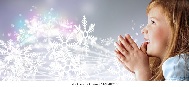 Portrait of young smiling praying girl looking up in blue dress against silver fairy snowstorm background
