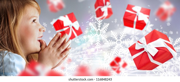 Portrait of young smiling praying girl looking up against silver fairy snowstorm background. Red gift boxes are flying around
