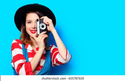 Portrait of young smiling red-haired white european woman in hat and red striped shirt with camera on blue background