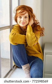 Portrait of young smiling red-haired woman sitting on windowsill