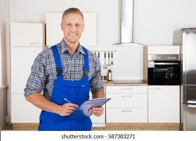 Portrait Of A Young Smiling Repairman Standing With His Clipboard In Kitchen At Home