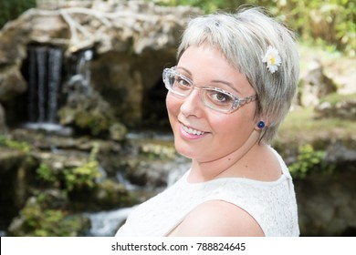 portrait of young smiling short hair woman in the summer park