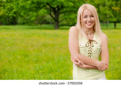Portrait of young smiling woman against summer nature.