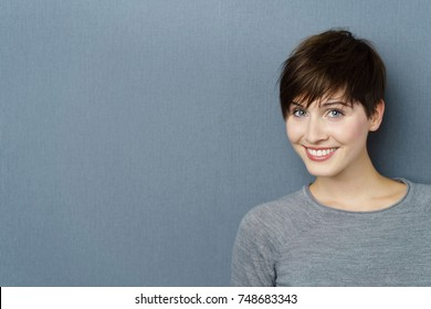 Portrait of young smiling woman against grey background