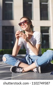 portrait of a young smiling woman in casual clothes sitting outdoors with paper cups of coffee in her hands. coffee to go
