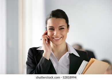 Portrait of young smiling woman with cell phone and documents