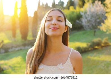 Portrait of young smiling woman with closed eyes and flower on ear taking deep breathing. Positive spring girl emotion face expression feeling life perception success peace mind concept.