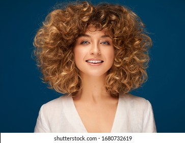 Portrait of young smiling woman with curly hair isolated on blue background