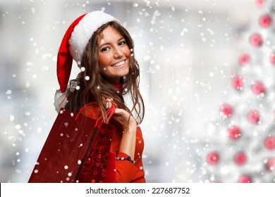 Portrait of a young smiling woman doing shopping before christmas