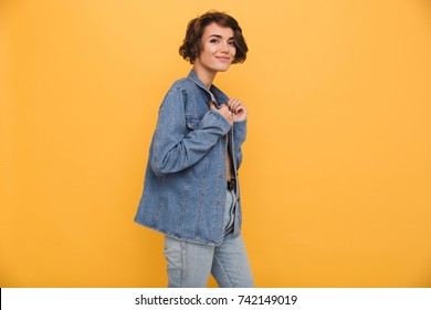 Portrait of a young smiling woman dressed in denim jacket posing while standing and looking at camera isolated over yellow background