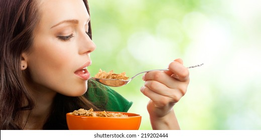 Portrait of young smiling woman eating muesli or corn flakes, outdoor, with blank area for copyspace