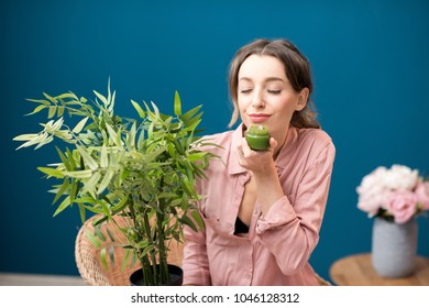 Portrait of a young smiling woman enjoying aroma cream sitting with green plant on the blue wall background at home