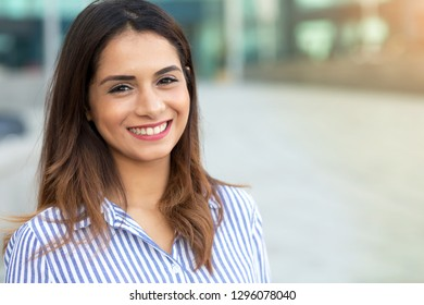 Portrait of young smiling woman outdoor with sunligth flare and copy space