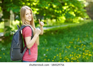Portrait of young smiling woman outdoors with copy space. Female student with backpack on green background of city park gesturing thumb up.