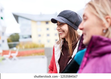 Portrait of a young smiling woman in red jacket,gray scarf and cap. Woman walking, talking and laughing outdoors on the street with girlfriend at sunny autumn or spring day