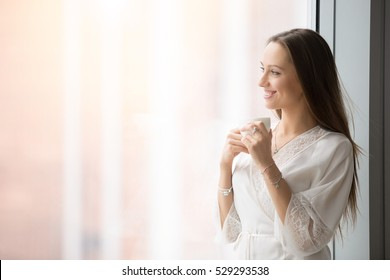 Portrait of young smiling woman standing at window wearing beautiful lingerie, jewelry and nightwear, preparing for very special evening, waiting for lover, dreaming and relaxing with cup of coffee