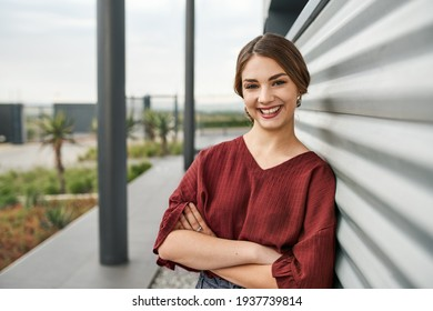 Portrait of young smiling woman student leaning on university campus wall with arms crossed