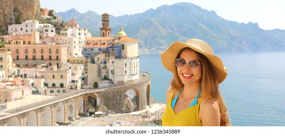 Portrait of young smiling woman with sunglasses in Atrani village, Amalfi Coast, Italy. Panoramic banner view of female tourist in her summer holidays in Southern Italy.