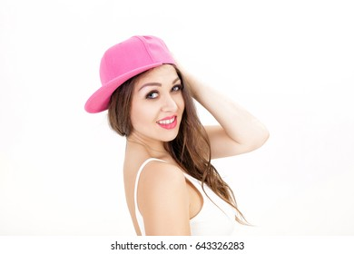 portrait of young smiling woman in white shirt and pink hat on white background