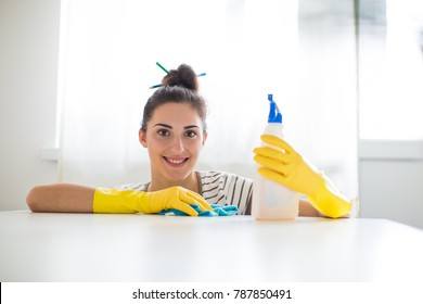 Portrait of the young smiling woman in yellow gloves who holding rag and detergent and sitting near table in the room