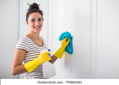 Portrait of the young smiling woman in yellow gloves who holding rag and detergent in hands and washing furnitures in the room