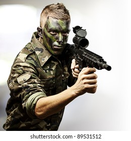 portrait of young soldier aiming with rifle against a abstract lights background