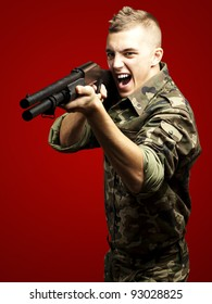 portrait of a young soldier aiming with shotgun against a red background