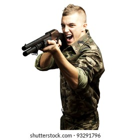 portrait of a young soldier aiming with a shotgun against a white background