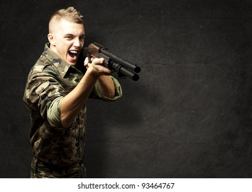 portrait of a young soldier aiming with shotgun against a grunge background