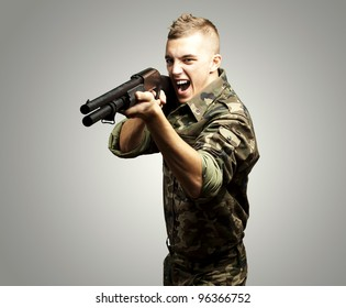 portrait of a young soldier aiming with shotgun over grey background