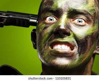 portrait of young soldier comitting suicide over green background
