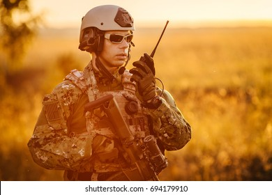 portrait of young soldier face with radio station against a sunset background