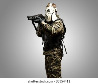 portrait of young soldier with gas mask aiming with shotgun