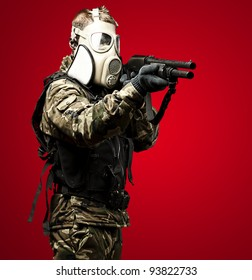 portrait of a young soldier with a gas mask aiming with a shotgun
