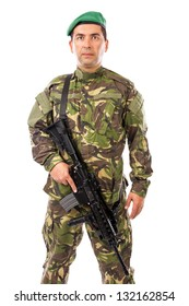 Portrait of a young soldier with a gun against white background