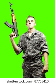 portrait of young soldier holding rifle against a removable chroma key background