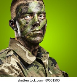portrait of young soldier with jungle camouflage paint on a green background