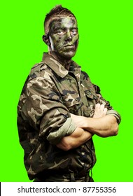 portrait of young soldier painted with jungle camouflage against a removable chroma key background