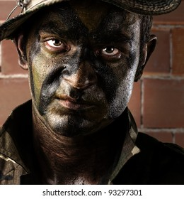 portrait of a young soldier painted with jungle camouflage against a brick wall