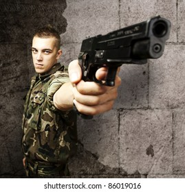 portrait of young soldier pointing with gun against a grunge background