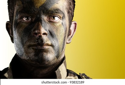 portrait of a young soldiers face with jungle camouflage paint against a yellow background