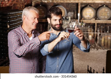 Portrait young sommelier standing at family wine cellar with senior winemaker and tasting a glass of red wine. Small business.