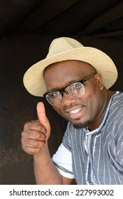 Portrait of a young South African black man with happy smiling facial expression, showing thumb-up and wearing glasses and straw hat. Image on dark blurry outdoor background.