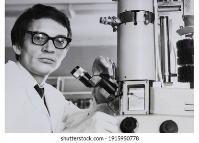 Portrait of young Soviet guy with glasses and white medical gown, with microscope. Vintage black and white paper photo. Early 1980s. Old surface, soft focus. Transferred property, family archive.
