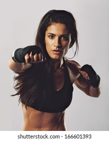 Portrait of young sport girl training boxing against grey background. Hispanic female practicing boxing looking at camera. Female boxer throwing a punch in front.