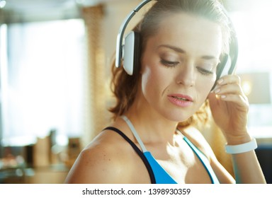 Portrait of young sports woman in sport clothes listening to the music with headphones in the modern house.