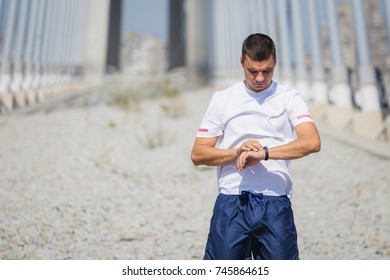 Portrait of young sportsman looking at his pulse heart rate smart watch